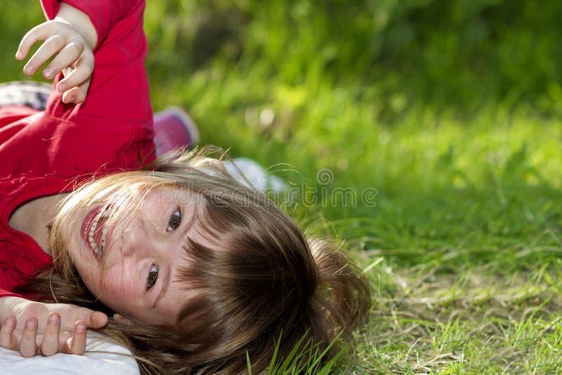 Nettes hübsches lächelndes Kindermädchen mit grauen Augen und langen angemessenen dem Haar, die den Spaß draußen legt auf grünes  lizenzfreies stockbild
