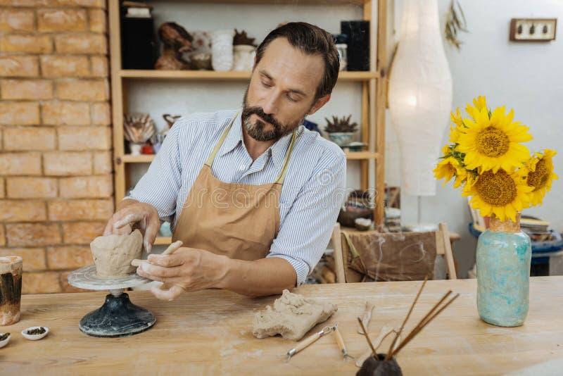Nettes handicraftsman, das nahe dem Vase mit Sonnenblumen arbeitet stockfotos