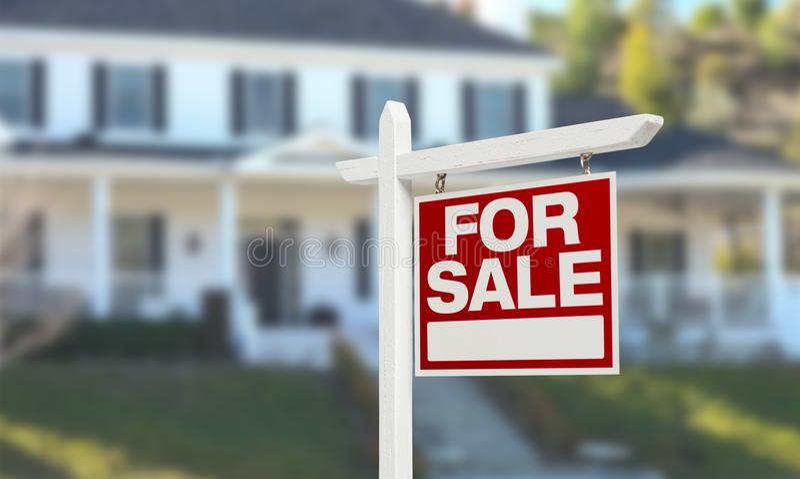 Nettes Haus für Verkaufs-Real Estate-Zeichen vor schönem neuem Haus lizenzfreie stockbilder