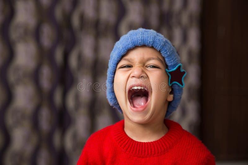 Nettes indisches Kind, das eine Haltung in der Winterabnutzung mit einem großen Lachen schlägt stockfotografie