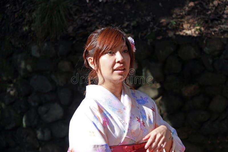 Nettes japanisches Mädchen im hellrosa Kimonokleid an Schrein Fushimi Inari lizenzfreie stockbilder