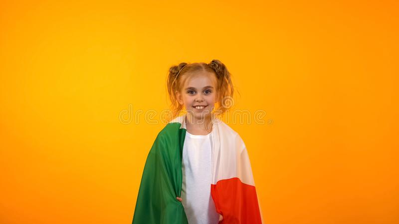 Nettes Jugendfanmädchen eingewickelt in der italienischen Flagge, die für Nationalmannschaft zujubelt stockfotografie