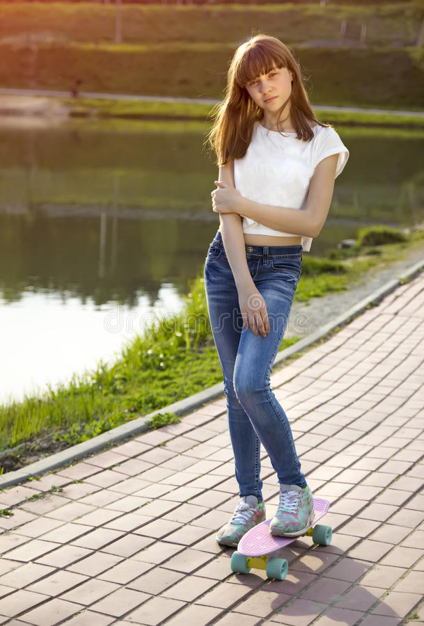 Nettes jugendlich Mädchen auf einem Skateboard auf der Straße stockfoto