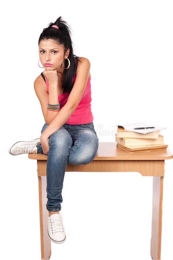 Nettes jugendlich Mädchen, das auf ihrem Schreibtisch sitzt stockbild