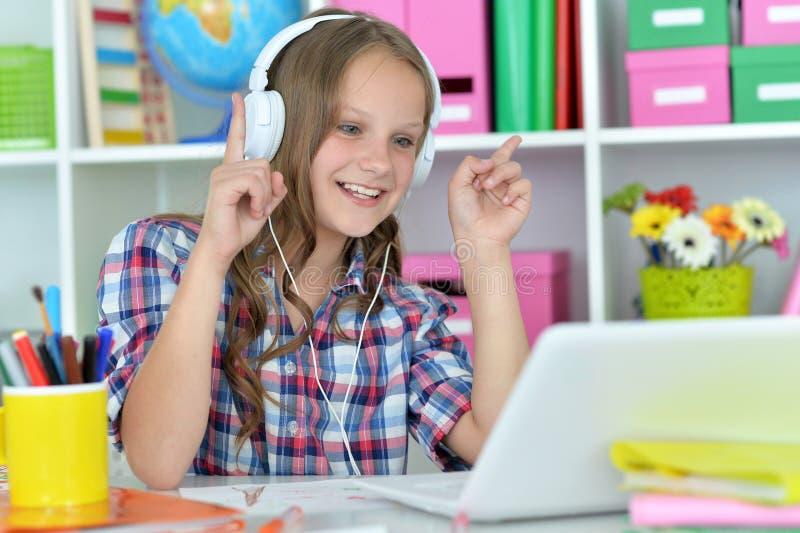 Nettes jugendlich Mädchen, das Laptop verwendet stockbilder