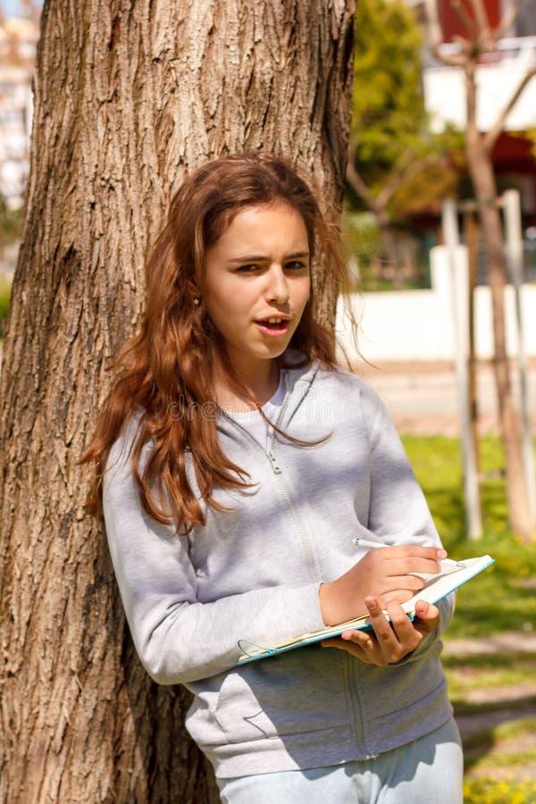 Nettes jugendlich Mädchen schreibt mit einem Stift in ein Notizbuch nahe in einen Park Selektiver Fokus lizenzfreie stockfotos