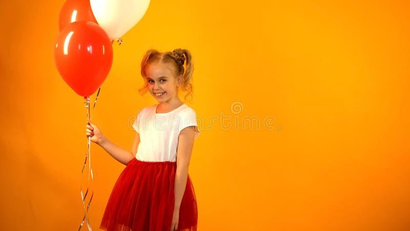 Nettes jugendliches Mädchen, das Luftballone hält und zur Kamera, Geburtstagsfeier schaut stockfotografie