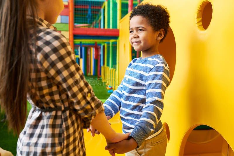 Nettes Jungen-Händchenhalten mit Mädchen auf Spielplatz lizenzfreies stockbild