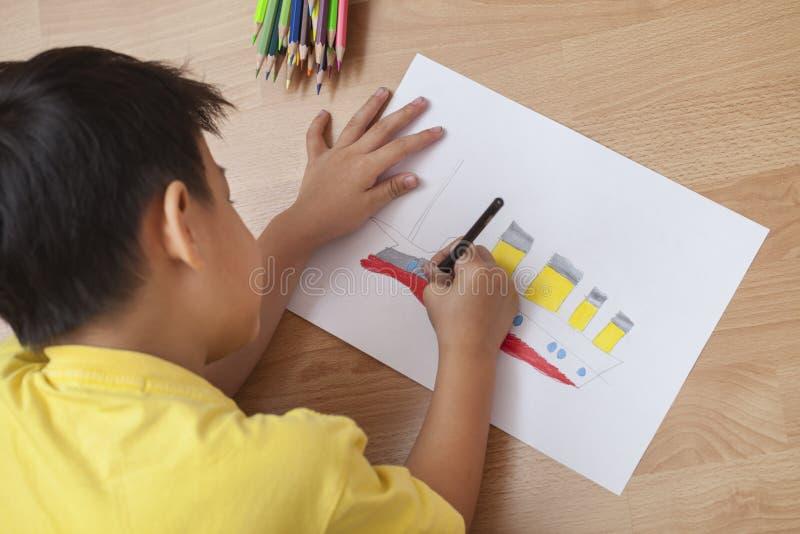 Nettes Jungenkind, das Hausarbeit, Färbungsseiten tut, das titanische Boot schreibt und malt lizenzfreies stockbild