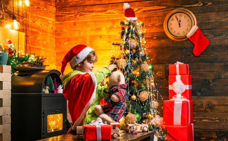 Nettes Jungenspiel nahe Weihnachtsbaum Kind genie?en Winterurlaub zu Hause Haus gef?llt mit Freude und Liebe Machen Sie Wunsch gu stockfotografie