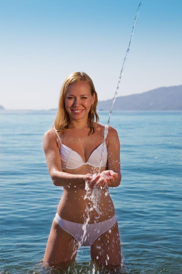 Nettes junges blondes im weißen Bikini, der Spaß hat stockfoto