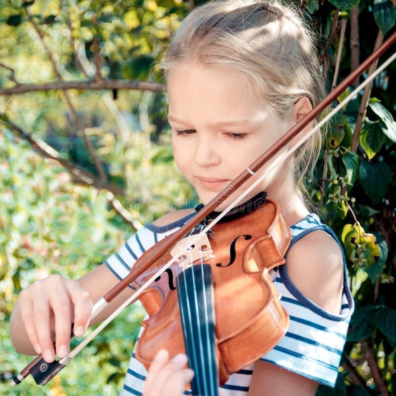 Nettes junges blondes M?dchen spielt die Violine im Garten am sonnigen Tag des Sommers lizenzfreies stockfoto