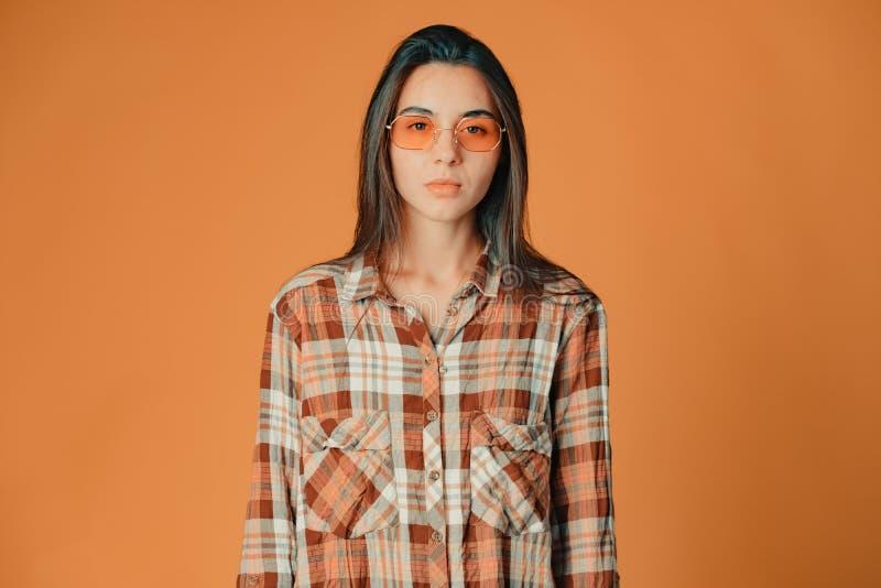Nettes junges brunette Mädchen, das Misstrauen auf orange Hintergrund zeigt stockfoto