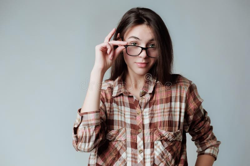 Nettes junges brunette Mädchen in lumbercheck Karohemd, das Kamera überrascht betrachtet stockbilder