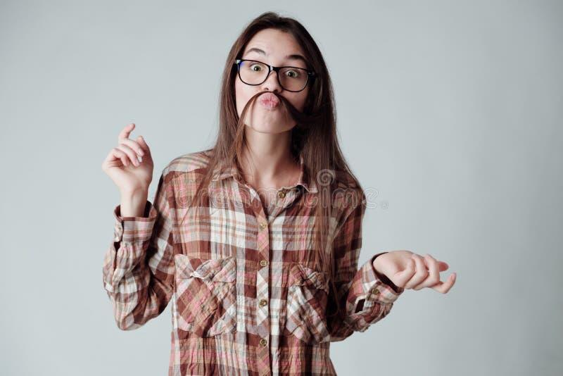 Nettes junges brunette Mädchen in lumbercheck Karohemd, das mit dem Haar spielt lizenzfreie stockfotografie