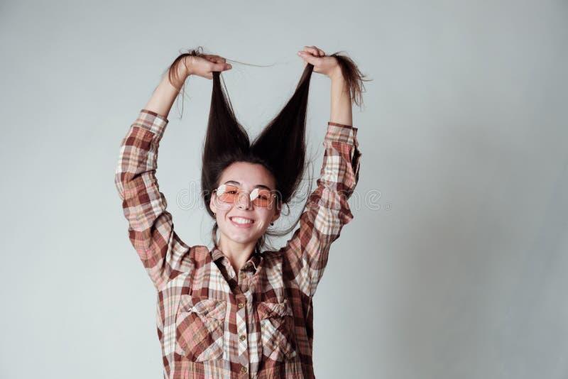 Nettes junges brunette Mädchen in lumbercheck Karohemd, das mit dem Haar spielt stockfotografie