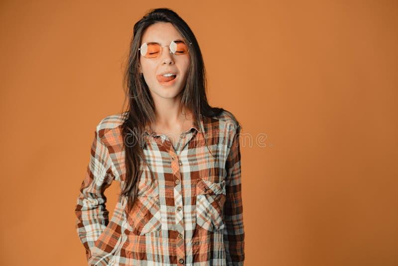 Nettes junges brunette Mädchen, wenn Zunge auf Kamera auf orange Hintergrund gezeigt wird stockbild
