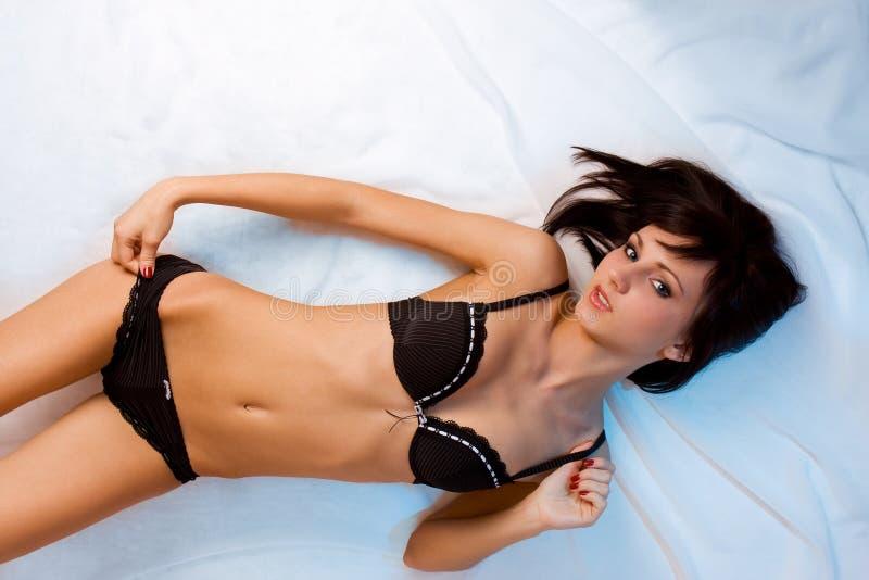 Nettes junges Brunettemädchen in der schwarzen Unterwäsche stockfotografie