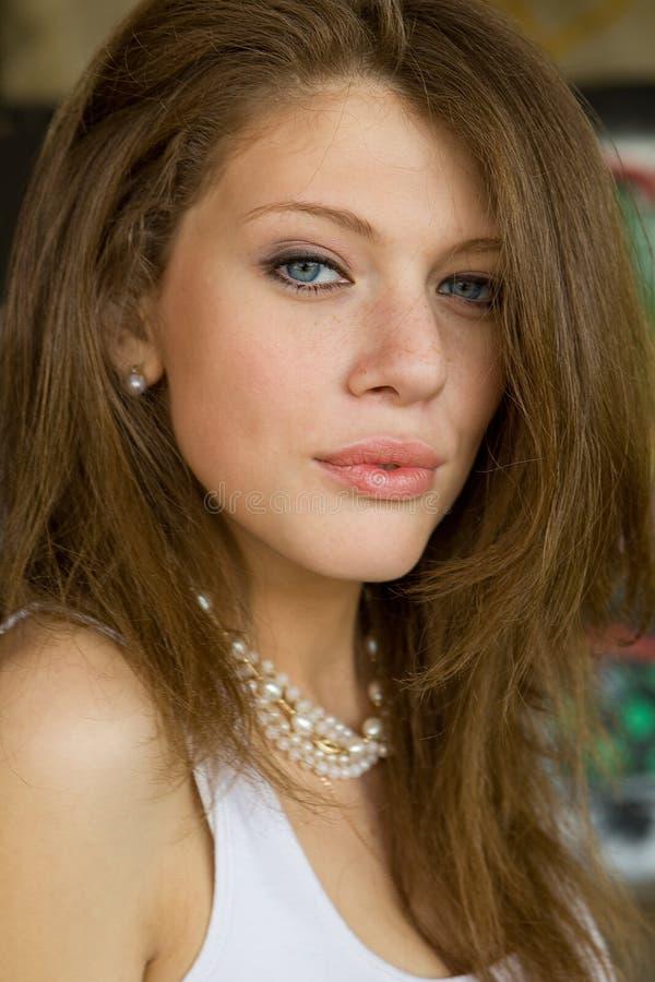 Nettes junges Brunettemädchenportrait in der weißen Bluse stockfoto