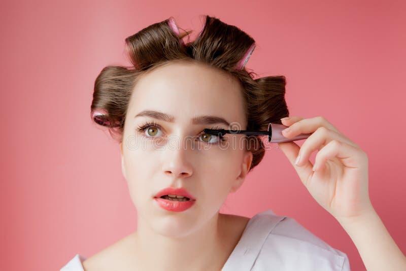 Nettes nettes junges das Mädchen im Lockenwickler malt eine Augenbraue auf rosa Hintergrund stockfotografie