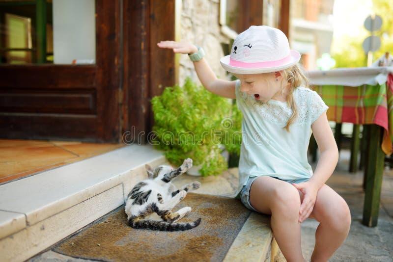 Nettes junges Mädchen, das eine freundliche griechische Katze am warmen und sonnigen Sommertag während der Familienurlaube in Kal lizenzfreie stockbilder