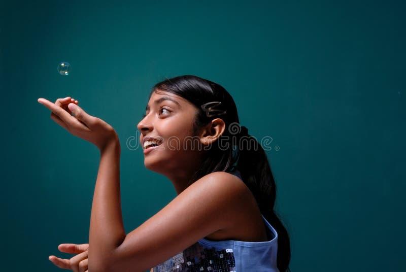 Nettes junges Mädchen, das mit einer Seifenluftblase spielt lizenzfreie stockfotos