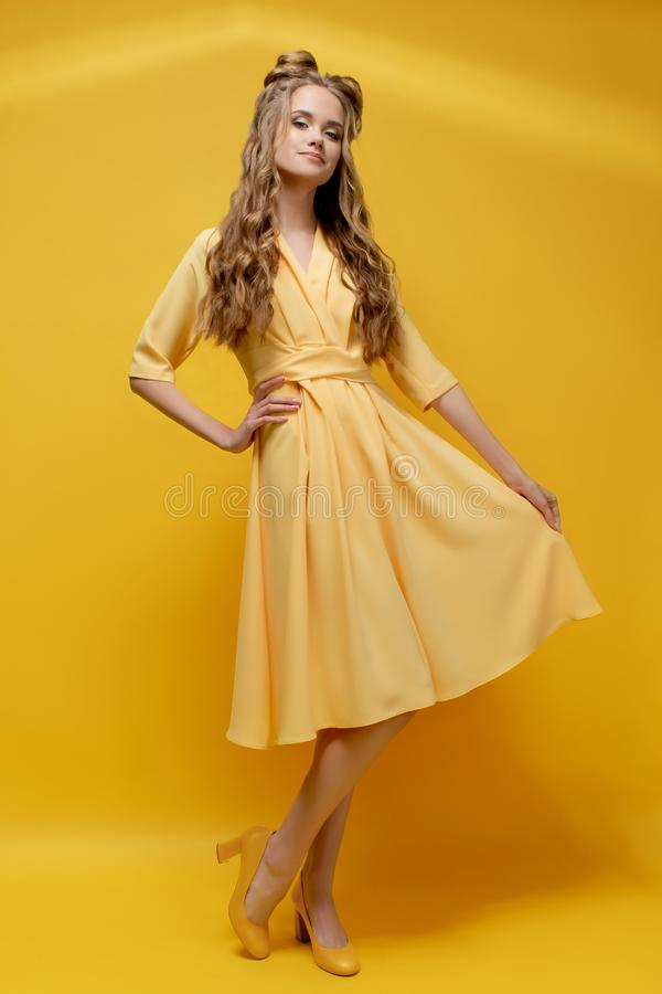Nettes junges Mädchen in einem gelben Kleid auf einem gelben Hintergrund mit einem Haarschnitt und einem gelockten langen Haar stockfotografie