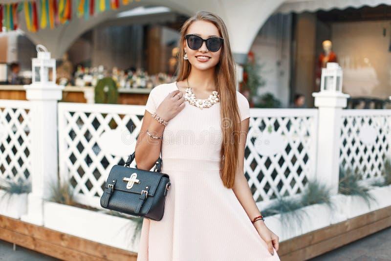 Nettes junges Mädchen in einem rosa Kleid mit Handtasche hat Spaß stockbild