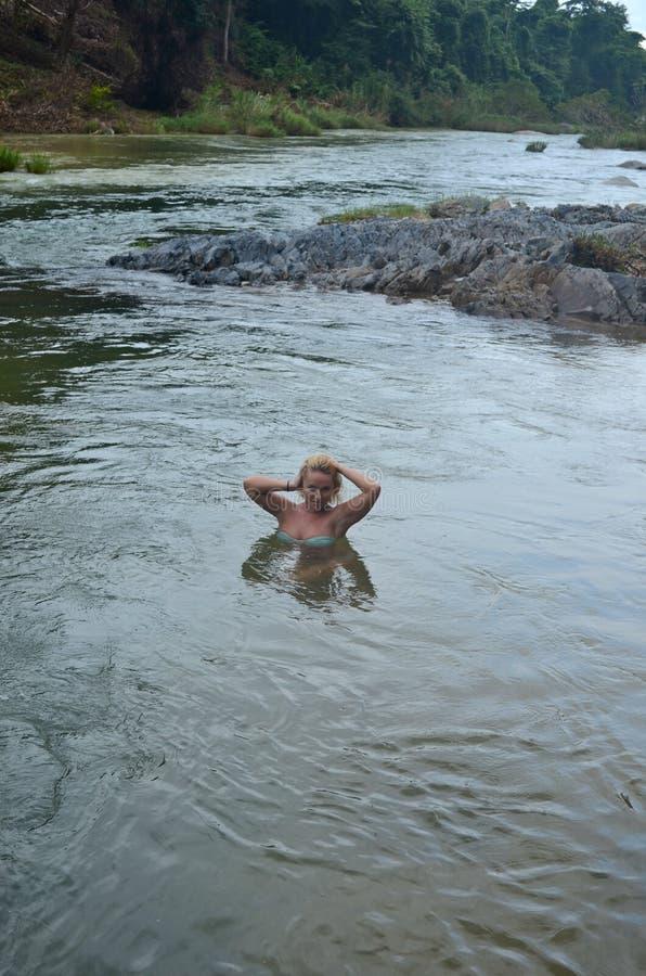 Nettes junges Mädchen ist im Fluss stockbilder