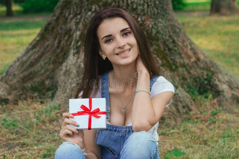 Nettes junges Mädchen am Park mit Geschenk in ihrem Hand-smilin stockfoto