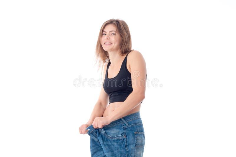 Nettes junges Mädchen trug große Hose und Lachen wird auf weißem Hintergrund lokalisiert stockbilder