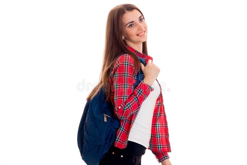 Nettes junges Studentenmädchen mit dem Rucksack, der weg schaut und Lächeln lokalisiert auf weißem Hintergrund Studentenjahrkonze stockbild