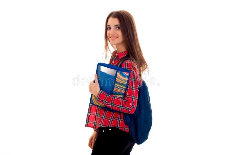 Nettes junges Studentenmädchen mit Rucksack und Ordner für die Notizbücher, welche die Kamera betrachten und Lächeln lokalisiert  stockfotografie