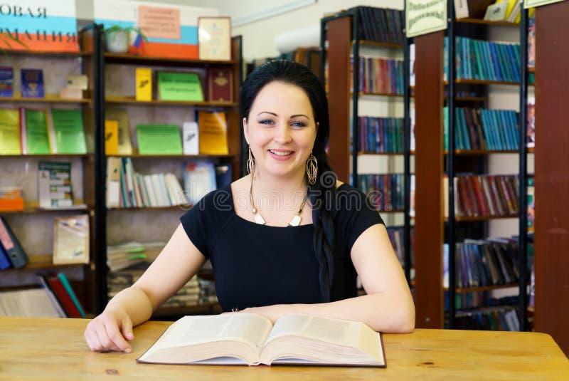 Nettes junges vorbildliches Mädchen, das Buch an der Bibliothek hält stockfotografie