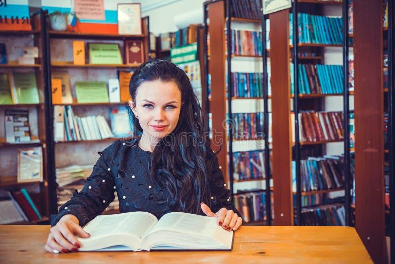 Nettes junges vorbildliches Mädchen, das Buch an der Bibliothek hält lizenzfreie stockfotografie