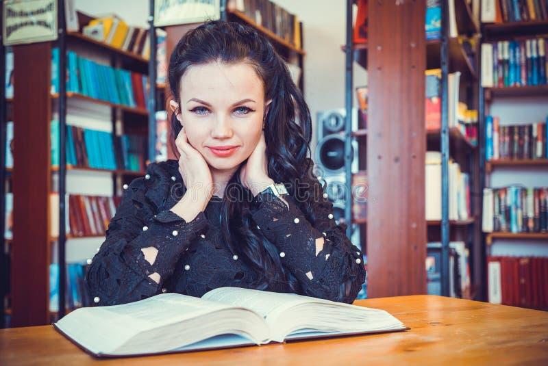Nettes junges vorbildliches Mädchen, das Buch an der Bibliothek hält lizenzfreie stockbilder