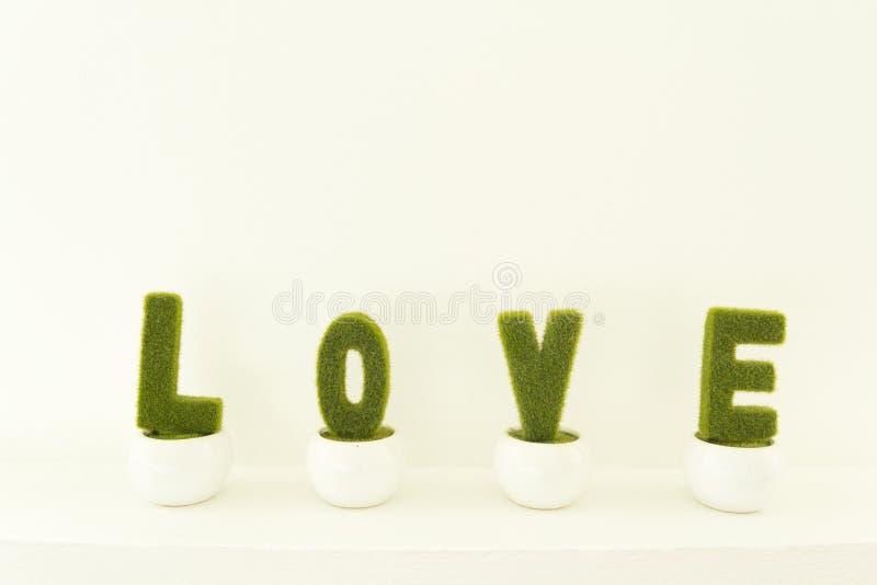 Nettes künstliches Gras wird als Charakter-Wort-Liebe auf weißem Blumentopf verziert stockfoto