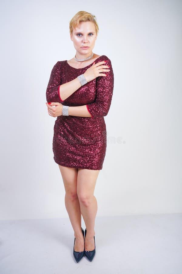 Nettes kaukasisches curvy Mädchen mit dem kurzen blonden Haar und Plusgrößenkörper, der schönes elegantes Kirschfarbkleid mit Pai stockfotografie