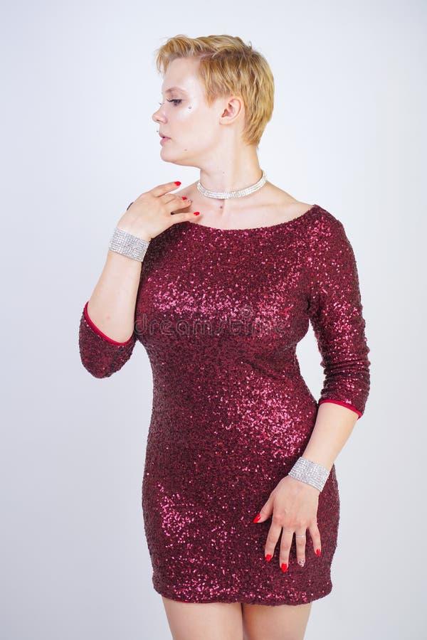 Nettes kaukasisches curvy Mädchen mit dem kurzen blonden Haar und Plusgrößenkörper, der schönes elegantes Kirschfarbkleid mit Pai lizenzfreie stockfotos