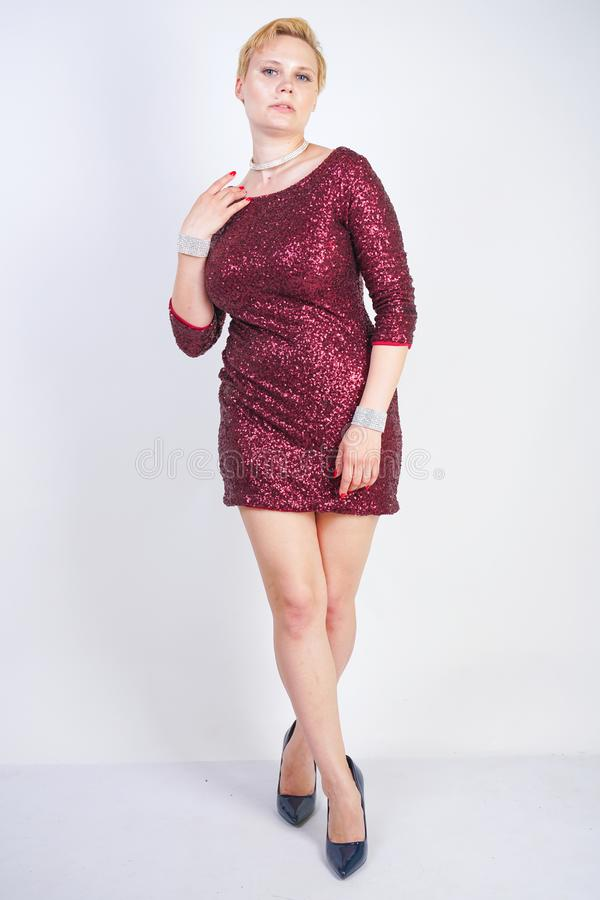 Nettes kaukasisches curvy Mädchen mit dem kurzen blonden Haar und Plusgrößenkörper, der schönes elegantes Kirschfarbkleid mit Pai lizenzfreie stockfotografie