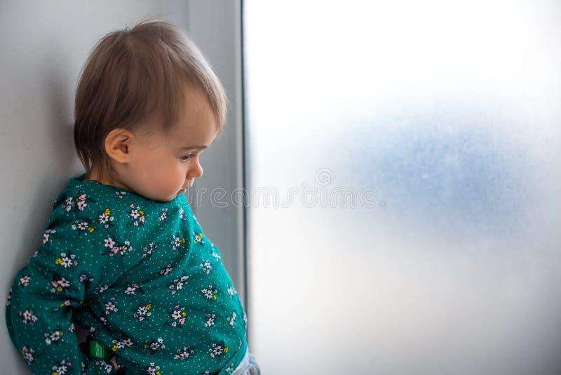 Nettes kaukasisches einjähriges Baby in der grünen Hemdstellung mit Rückseite gegen Wand nahe bei hellem Fenster lizenzfreies stockfoto