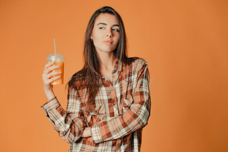 Nettes kaukasisches junges brunette Mädchen, das Orangensaft auf orange Hintergrund hält lizenzfreies stockfoto