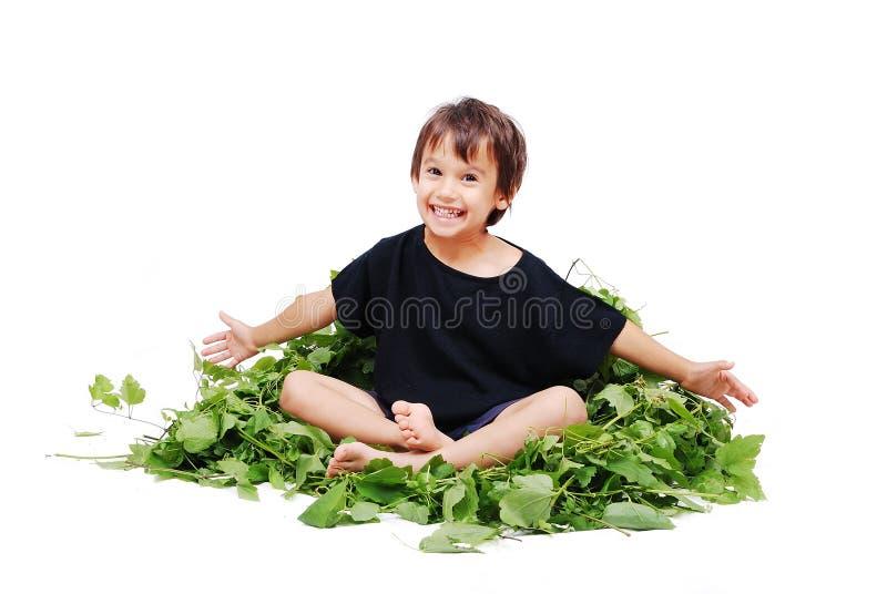 Nettes Kind, das auf Blättern sitzt lizenzfreie stockfotografie