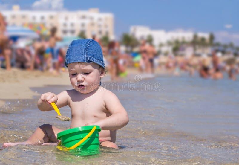 Nettes Kind, das auf dem Strand mit Sand und Wasser spielt lizenzfreies stockbild
