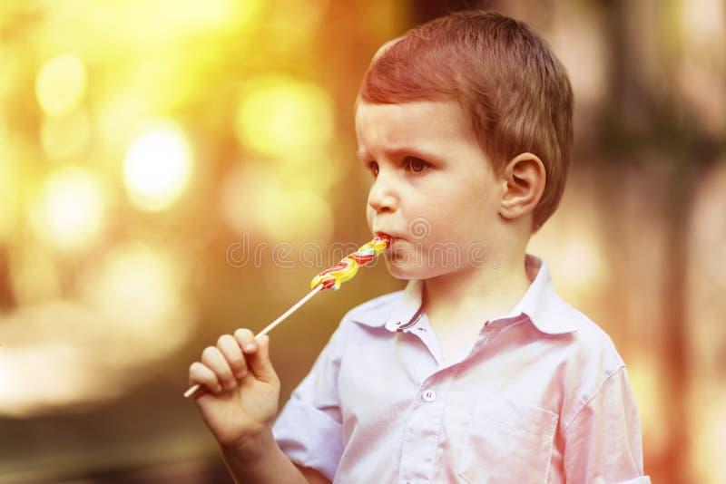 Nettes Kind, das auf einem Lutscher saugt stockfotografie
