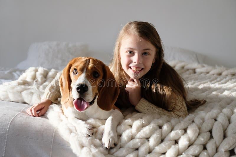Nettes Kind, das beim Spürhundhund auf dem Sofa liegt Spürhund und Mädchen, welche zusammen die Kamera betrachten Lustiger Hund u lizenzfreies stockfoto