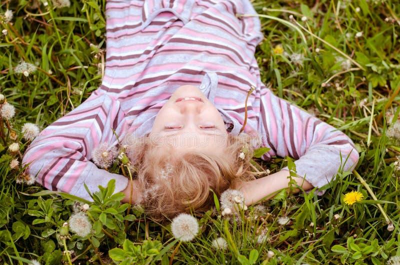 Nettes Kind, das in der Löwenzahnwiese liegt lizenzfreies stockfoto