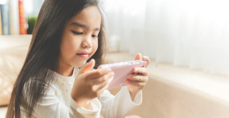 Nettes Kind, das einen Smartphone verwendet und beim Sitzen auf Sofa lächelt lizenzfreie stockfotografie