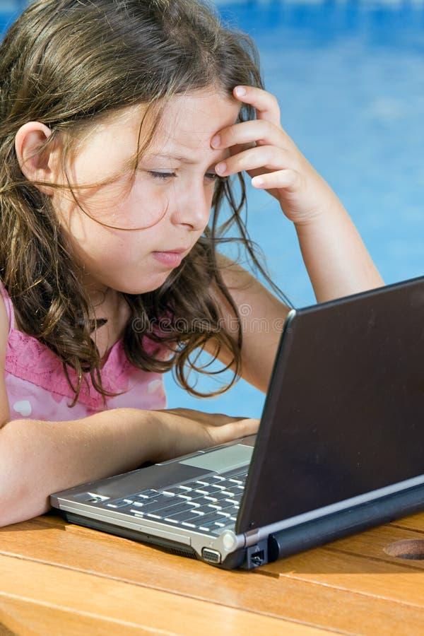 Nettes Kind, das ihren Laptop durch das Pool verwendet stockfotografie