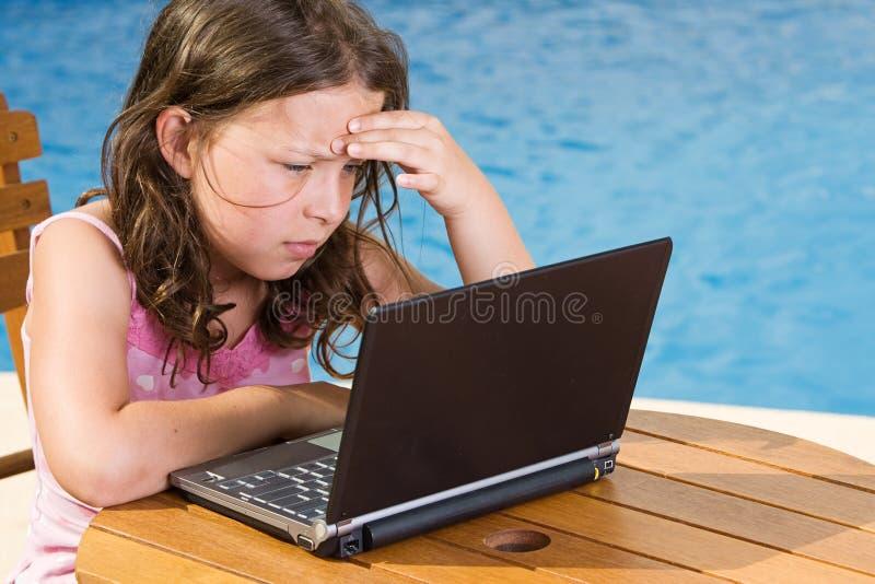 Nettes Kind, das ihren Laptop durch das Pool verwendet stockfotos